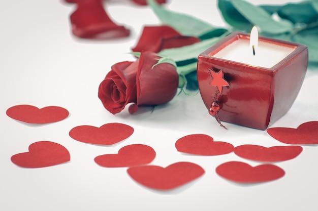 Brennende kerze und rote rose auf weißem hintergrund