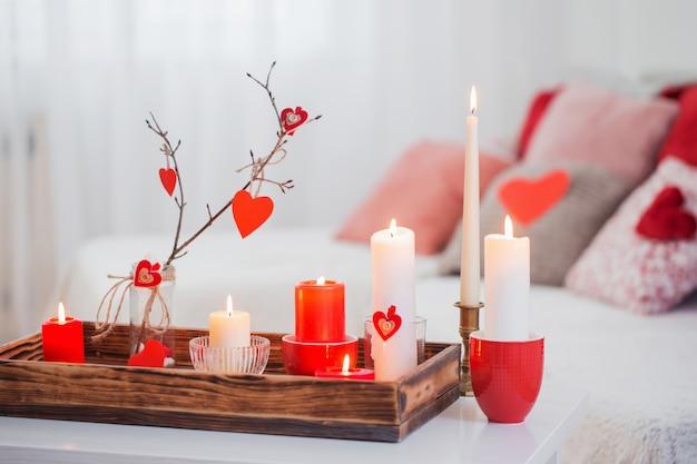 Brennende kerzen auf weißem tisch im innenraum. valentinstag konzept