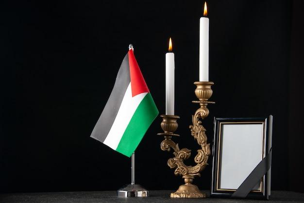 Brennende kerzen der vorderansicht mit palästinensischer flagge und dunkler oberfläche des bilderrahmens