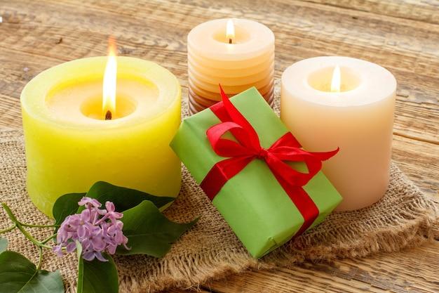 Brennende kerzen, geschenkbox und lila blumen auf sackleinen und alten holzbrettern.