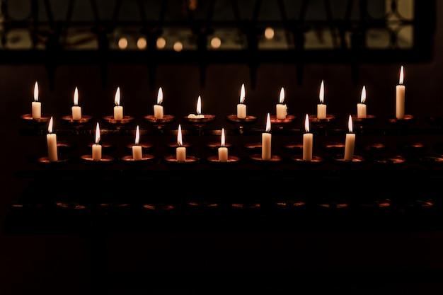Brennende kerzen in der kirche auf dunklem hintergrund