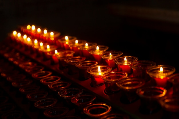 Brennende kerzen in einem tempel in folge in der dunkelheit. nahansicht. . copyspace.