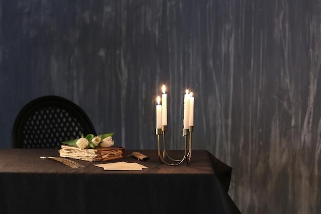 Brennende kerzen mit altem buch und blumen auf tisch