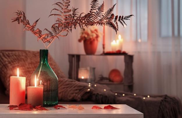 Brennende kerzen mit herbstdekor auf weißem tisch zu hause