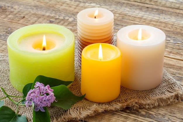 Brennende kerzen mit lila blumen auf sackleinen und alten holzbrettern. ansicht von oben.