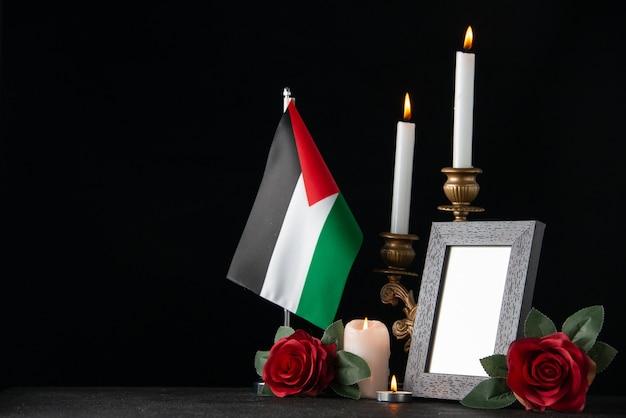 Brennende kerzen mit palästinensischer flagge und blumen auf der dunklen oberfläche