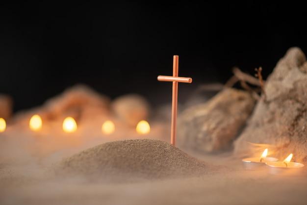 Brennende kerzen mit steinen um kleines grab als erinnerung an den tod der beerdigung