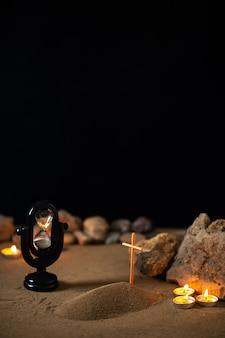 Brennende kerzen mit steinen und kleinem grab auf sand als erinnerung an den tod der beerdigung