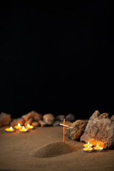 Brennende kerzen mit steinen und kleinem grab auf sand als todesbestattung