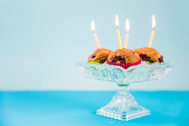 Brennende kerzen über dem kleinen kuchen auf blauem hintergrund