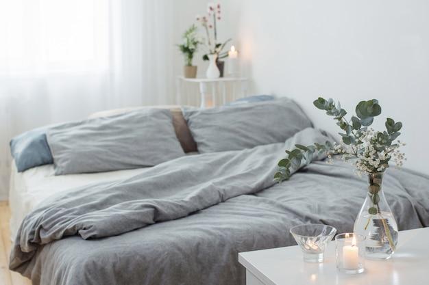 Brennende kerzen und eukalyptus in glasvase im weißen schlafzimmer
