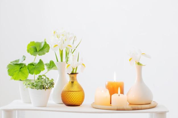 Brennende kerzen und frühlingsblumen auf holzregal im weißen innenraum