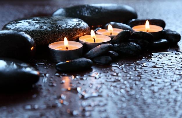 Brennende kerzen und wassertropfen. steintherapie. spa behandlung.
