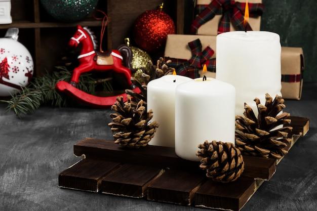 Brennende kerzen und weihnachtsattribute auf einer dunklen oberfläche