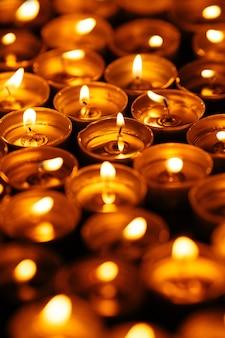Brennende kerzen. viele gelbe kerzen leuchten im dunkeln. nahansicht
