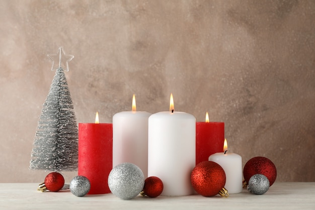 Brennende kerzen, weihnachtsbaum und kugeln auf braun