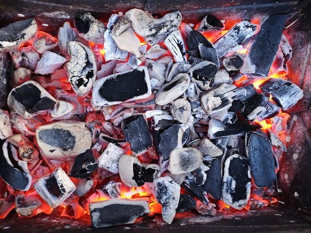 Brennende kohlen und brennholz auf dem grillrost. vorbereitung der kohle zum grillen im offenen grill. das konzept der entspannung und des essens. schöne kohlen. kochfertige kohlen.
