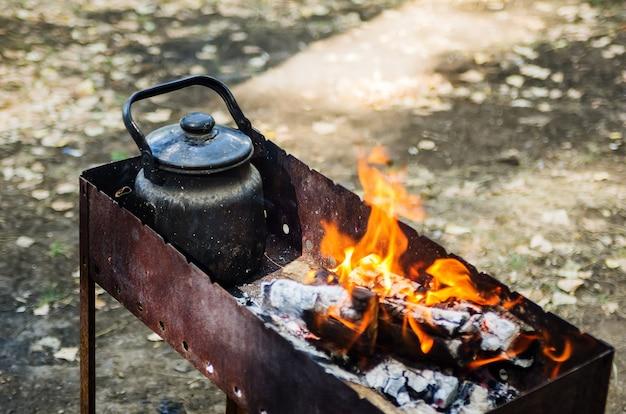 Brennende kohlenpfanne mit einem wasserkocher