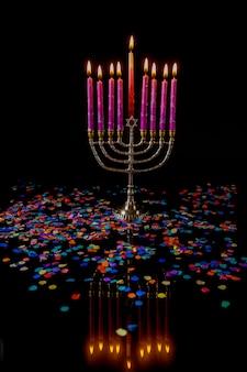 Brennende menora mit rosa kerzen und konfetti auf schwarzem hintergrund. jüdisches feiertags-chanukka-symbol.