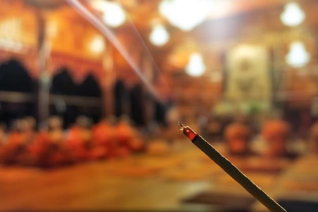 Brennende räucherstäbchen mit rauch, räucherstäbchen, die an einem weinlese buddhistischen tempel brennen