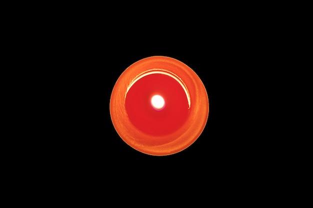 Brennende rote kerze auf schwarzem hintergrund. speicherkonzept. ansicht von oben.