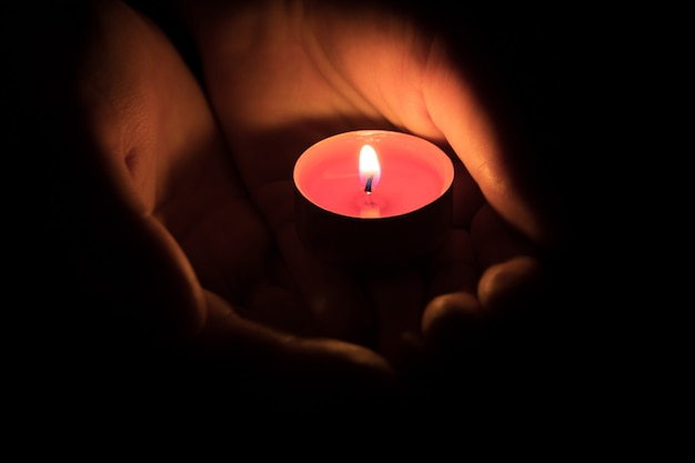 Brennende rote kerze in den handflächen in der dunkelheit speicherkonzept