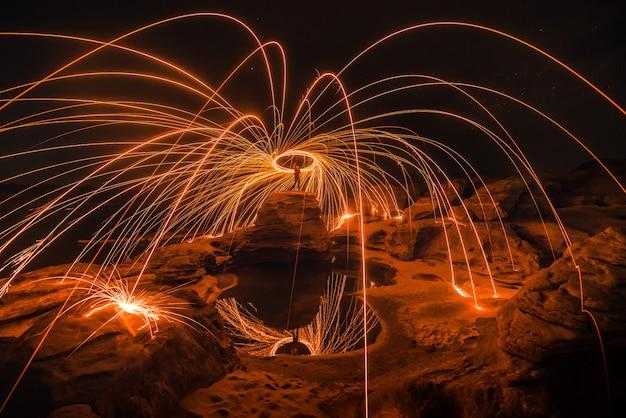 Brennende stahlwolle auf dem felsen nahe dem fluss bei sam phan bok in ubonratchathani ungesehen in thailand