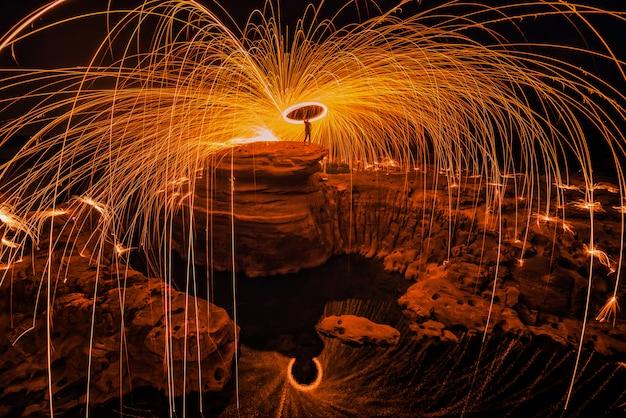 Brennende stahlwolle auf dem felsen nahe dem fluss.
