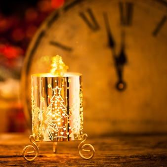 Brennende weihnachtskerze gegen vintage uhr. neujahrskonzept
