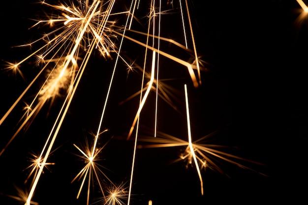Brennende wunderkerze auf einem schwarzen hintergrundbild