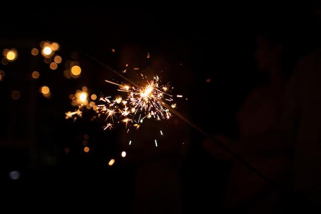 Brennende wunderkerze bei dunkelheit. platz für text. frohes neues jahr und frohe weihnachten konzept. schöne ferien