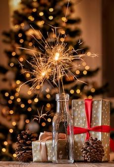 Brennende wunderkerzen in glasflasche mit weihnachtsdekoration