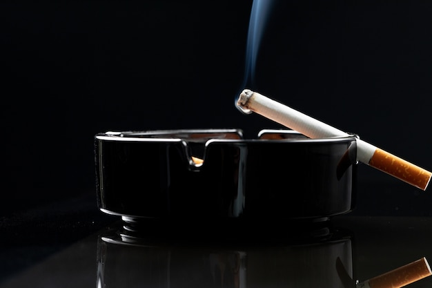 Brennende zigarette in einem schwarzen aschenbecher nahaufnahme