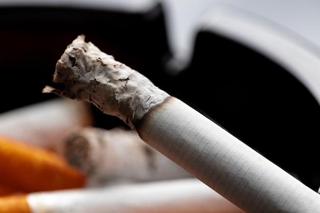 Brennende zigarette in einem schwarzen aschenbecher
