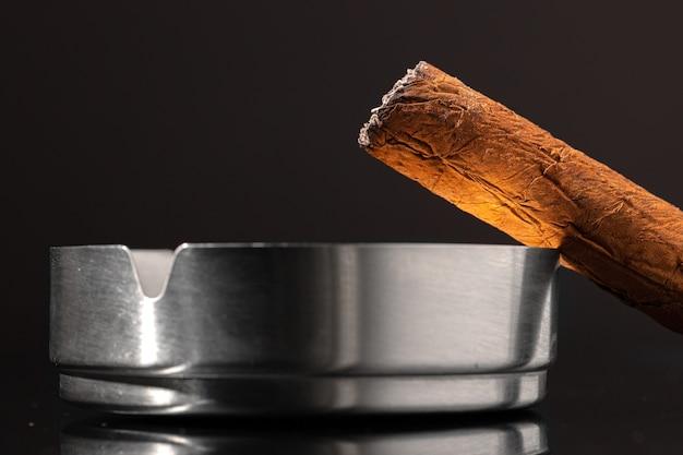 Brennende zigarre gegen schwarzen hintergrund schließen