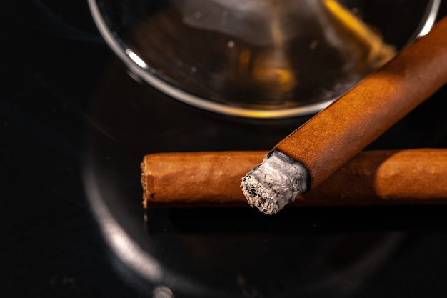 Brennende zigarre gegen schwarzen tisch hautnah