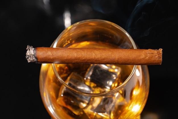 Brennende zigarre und glas whisky auf schwarzem hintergrund schließen