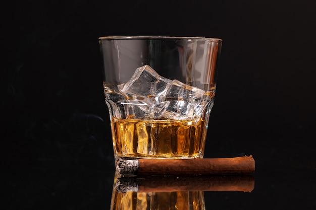 Brennende zigarre und glas whisky auf schwarzem hintergrund