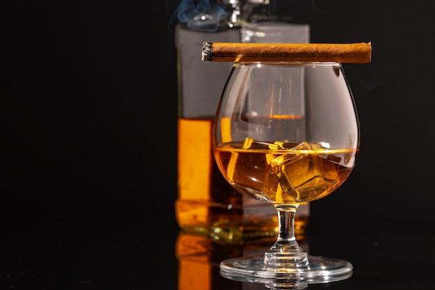 Brennende zigarre und glas whisky auf schwarzem tisch