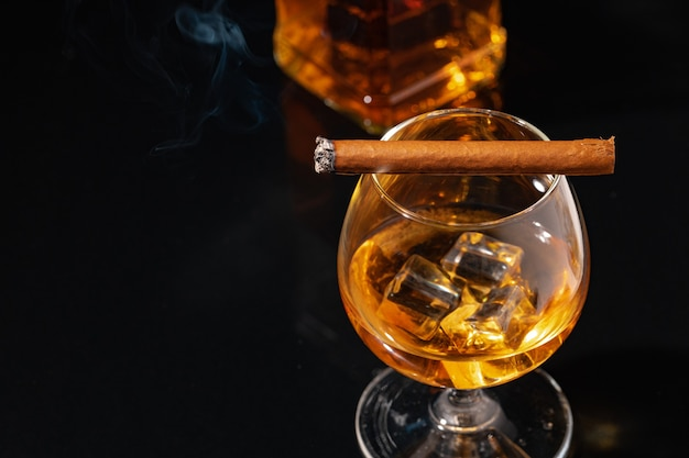 Brennende zigarre und glas whisky auf schwarzer nahaufnahme