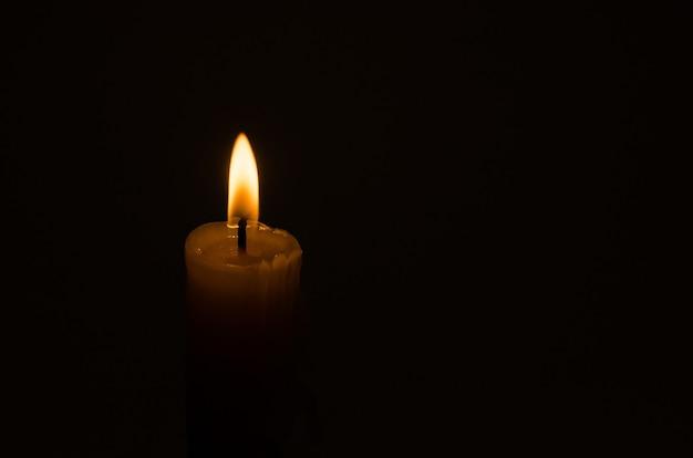 Brennender kerzendocht auf schwarzem hintergrund mit kopierraum, traurigkeit und trauerkonzept.