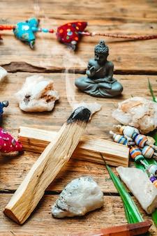 Brennender palo santo hintergrund mit kristallen und edelsteinen. reinigungsbündel mit heilenden mineralien und kerzen. entspannen sie sich und legen sie sich flach