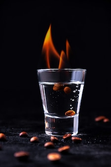 Brennender sambuca im glas mit kaffeebohnen auf dunkler wand. concept shot alkohol cocktails
