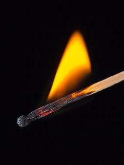 Brennender streichholzstab in der hand auf einem schwarzen isolierten hintergrund.