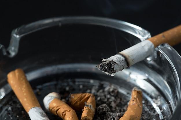 Brennender zigarettenstummel im aschenbecher