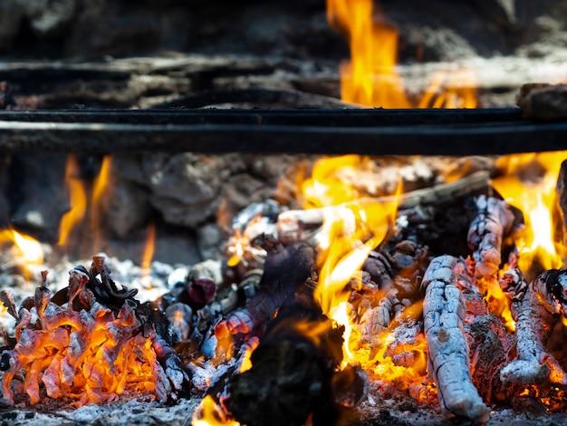 Brennendes brennholz mit heller flamme und flackernden kohlen