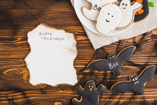 Brennendes papier nahe halloween-lebkuchen auf platte