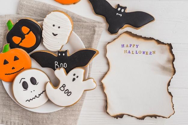 Brennendes papier nahe halloween-lebkuchen auf teller