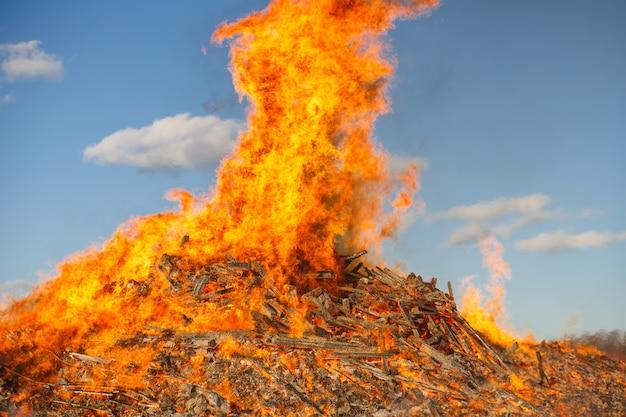 Brennendes riesiges feuer gegen den blauen himmel.