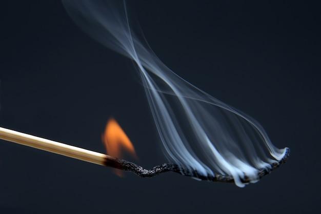 Brennendes streichholz auf einem dunklen blau